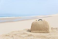 Maleta hecha fuera de la arena en la playa foto de archivo