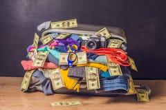 Maleta llena con los accesorios y el dinero del viaje en fondo de madera Fotografía de archivo libre de regalías