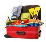 Maleta llena a las vacaciones, equipaje rojo abierto por completo de ropa Fotos de archivo libres de regalías