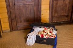 Maleta por completo de cosas en la puerta Foto de archivo libre de regalías