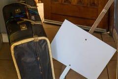 Maleta retra de la cartulina y un cartel en blanco fuera de una puerta abierta Fotografía de archivo