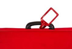 Maleta roja con la etiqueta en blanco sobre blanco. Primer. Imagen de archivo