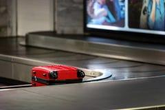 maleta roja que espera para ser cogido  Imagen de archivo libre de regalías