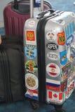 Maleta viajada bien, con las etiquetas engomadas internacionales, multicoloras fotos de archivo libres de regalías