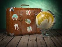 Maleta vieja con el globo en el fondo de madera Viaje o turismo c imagen de archivo libre de regalías