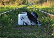 Maleta vieja con la inscripción BERLÍN PARÍS y el sombrero en pistas ferroviarias Foto de archivo