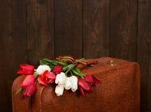 Maleta vieja con las flores, símbolo de la victoria en la Segunda Guerra Mundial con la cinta del ` s de San Jorge, un fondo de m Imagen de archivo libre de regalías