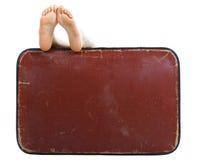 Maleta vieja con los pies femeninos descubiertos en tapa Imágenes de archivo libres de regalías