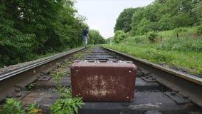 Maleta vieja en línea ferroviaria almacen de metraje de vídeo