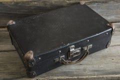 Maleta vieja en un viejo fondo de madera Foto de archivo
