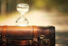 Maleta y reloj de arena aislados con el fondo de la falta de definición Fotos de archivo libres de regalías