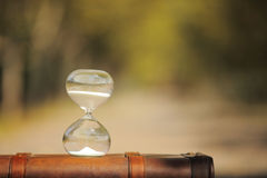 Maleta y reloj de arena con el fondo de la falta de definición Foto de archivo libre de regalías