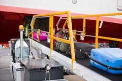 Maletas en el transportador móvil atado al aeroplano Fotos de archivo