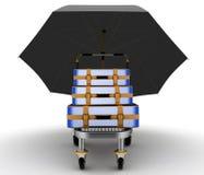 Maletas en la carretilla de la carga debajo del paraguas en blanco Fotos de archivo libres de regalías
