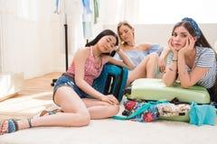 Maletas que embalan de las mujeres para las vacaciones junto en casa, embalando concepto del equipaje Imagen de archivo