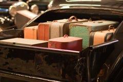 Maletas retras en cama del carro clásico Imagen de archivo libre de regalías