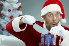 Malevolent Santa. Thief in costume of Santa Claus cutting Christmas gift boxes Stock Image