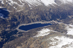 Malga Boazzo lake and dam, Italy. Aerial shot, from a small plane, of Malga Boazzo mountain lake and dam, shot on a bright springtime day in Brescia mountains Royalty Free Stock Photos