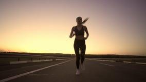 Malgrado la grande ragazza di sport di affaticamento impegnata nel pareggiare nella sera al tramonto video d archivio
