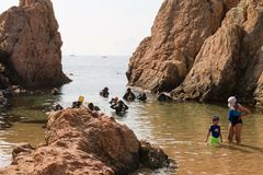 Malgrat de Mar, Catalonia, Spain, August 2018. A group of divers preparing to dive, a little boy imitating adults. Sea, sun, rocks, divers in suits for scuba royalty free stock image