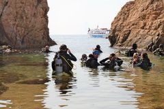 Malgrat de Mar, Catalonia, Spain, August 2018. A group of divers is preparing to dive into the Mediterranean Sea. People in suits for scuba diving, lagoon stock photo