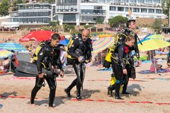 Malgrat de Mar, Catalonia, Spain, August 2018. A group of very tired divers returns after diving. Tired but satisfied faces of people, sand of the beach stock image