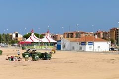Malgrat de Mar, Catalonia, Spain, August 2018. Garbage cans and scavengers on the background of a circus tent and the police stati. Malgrat de Mar, Catalonia stock image