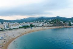 Malgrat de Mar, Catalonia, Spain, August 2018. View of the beach, the city and the distant mountains from the walls of the old for. Tress.Blue sky with clouds stock images