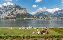 People resting on the Lakefront of Malgrate located on the shore of Como Lake in province of Lecco. Malgrate, Lombardy, Italy - August 28, 2015: People resting Stock Photography