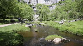 Malham Cove stream at the bottom of the rocks Yorkshire Dales National Park UK popular visitor attraction