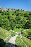 Malham Cove, Yorkshire Dales, England. Walking paths leading to the limestone cliffs of Malham Cove in the Yorkshire Dales, England, UK Royalty Free Stock Image