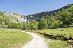 Malham Cove Yorkshire Dales National Park Tourist Attraction. Malham Cove is a limestone formation in Yorkshire Dales National Park, England. The large, curved Stock Photo