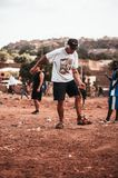 Black african children playing soccer with caucasian volunteer stock photos