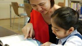 Mali Azjatyccy ucznie i nauczyciel czytelnicza książka w bibliotece wpólnie zdjęcie wideo