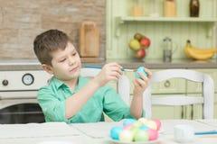 Mali blondyny żartują chłopiec kolorystyki jajka dla Wielkanocnego wakacje w domowej kuchni zdjęcia stock