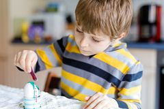 Mali blondyny żartują chłopiec kolorystyki jajka dla Wielkanocnego wakacje w domowej kuchni, indoors obrazy stock