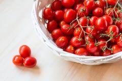 Mali czerwoni czereśniowi pomidory w łozinowym koszu na starym drewnianym stole obrazy royalty free