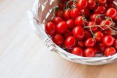 Mali czerwoni czereśniowi pomidory w łozinowym koszu na starym drewnianym stole zdjęcia stock