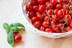 Mali czerwoni czereśniowi pomidory w łozinowym koszu na starym drewnianym stole obrazy stock