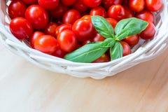 Mali czerwoni czereśniowi pomidory w łozinowym koszu na starym drewnianym stole zdjęcia royalty free