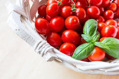 Mali czerwoni czereśniowi pomidory w łozinowym koszu na starym drewnianym stole zdjęcie royalty free