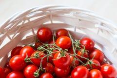 Mali czerwoni czereśniowi pomidory w łozinowym koszu na starym drewnianym stole fotografia stock