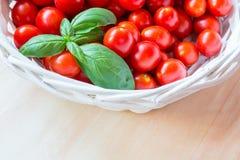Mali czerwoni czereśniowi pomidory w łozinowym koszu na starym drewnianym stole fotografia royalty free