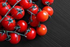 Mali czerwoni pomidory na winogradzie na czarnym drewnie od above Fotografia Stock