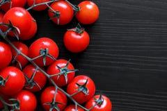 Mali czerwoni pomidory na winogradzie na czarnym drewnie od above Obrazy Stock