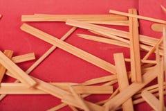 Mali Drewniani kije mieszaj? na czerwonym tle zdjęcie stock