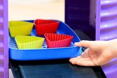 Mali dzieci bawią się Dziecka ` s sztuki kuchnia Dziecko dostaje z piekarnika zabawkarskich foremek z imaginacyjnymi babeczkami D Zdjęcie Royalty Free