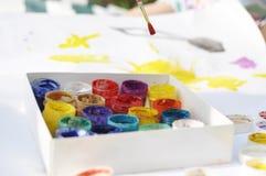 Mali dzieci malują z farbami i muśnięcia na ampule ciąć na arkusze na ulicie na słonecznym dniu, twórczości i zabawie, zdjęcie stock