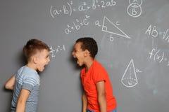 Mali dziecko w wieku szkolnym i matematycznie formuły fotografia stock