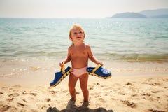 mali dziewczyna stojaki na piasku trzymają ojców kapcie lazurowym morzem Obraz Royalty Free